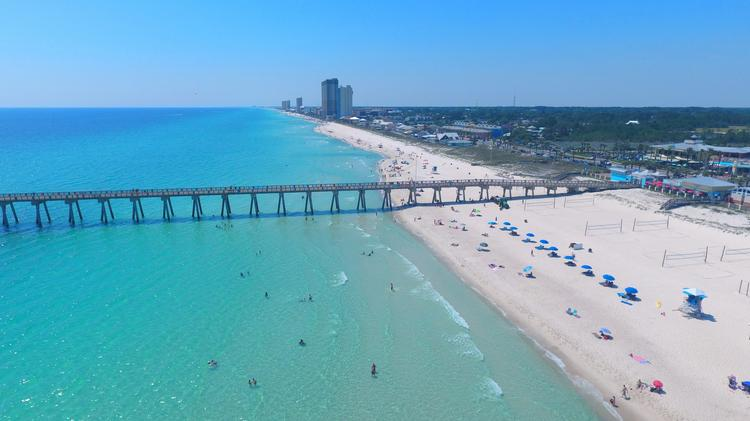 Vacationers Spread Out On The Sand By Scenic Pier In Panama City Beach Florida