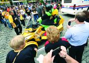 Fans take photos as the Pirate Parrot maneuvers a trike away from the crowd following the Pirates playoff rally in Market Square.