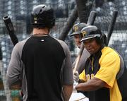 On his first day with the team, Pittsburgh Pirates outfielder Marlon Byrd, right, shares batting tips with Garrett Jones during batting practice at PNC Park on Aug. 28.