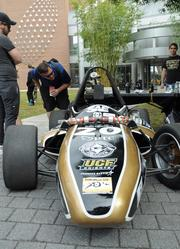 Students check out a formula-style race car designed and built by the UCF Society of Automotive Engineers. Each year, the group builds an open cockpit racer for competition in time trials.