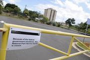 A sign on the gate at a parking lot at the USS Arizona Memorial at the World War II Valor in the Pacific National Monument at Pearl Harbor Tuesday informed visitors the attraction was closed because of the federal government shutdown.