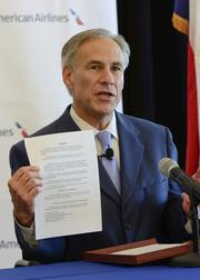 Texas Attorney General Greg Abbott holds the written agreement reached to end state's opposition to the proposed $11 billion merger.