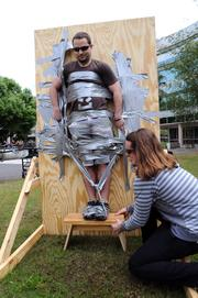 It may look like a rush week prank, but the duct tape wall is an exercise in defying gravity. The winning designer will successfully suspend his subject off the ground.