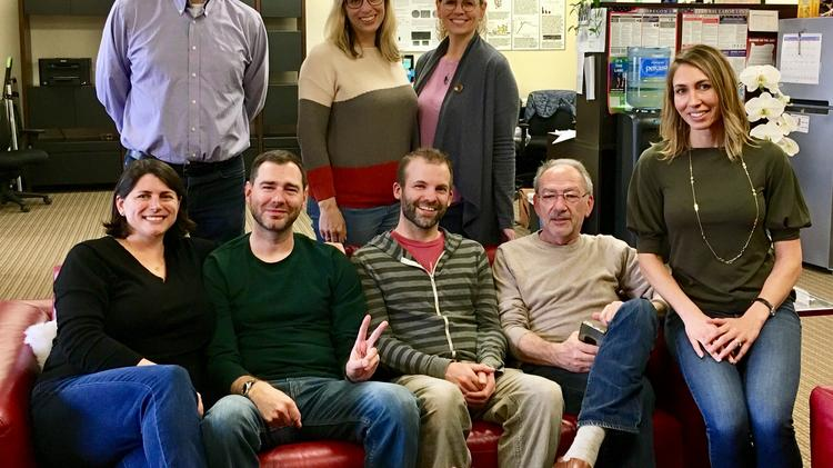 The eight-member Aronora team, including co-founder Erik Tucker, second from the left on the sofa, and Andras Gruber, second from the right.