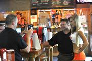 Customers pose for a photo with a Hooters Girl.