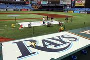 Rays groundskeepers paint use the MLB stencil along the first base line.
