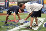 Rays groundskeepers Mike Deubel and Jason Hess paint along the first base line.
