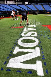 Rays groundskeeper James Michael, paints the MLB logo along the first base line.