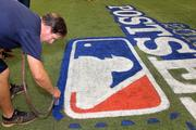 Rays groundskeeper Mike Deubel paints The MLB logo along the first base line.