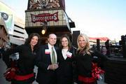 Center, Jose Valiente and Norma Berrios with CliftonLarsonAllen LLP pose with Buccaneers cheerleaders.