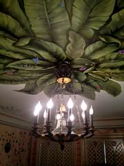 A light fixture at the mansion, with painted ceiling above.
