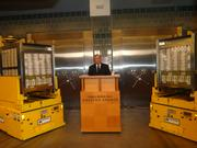 Richard Fisher, president and CEO of the Federal Reserve Bank of Dallas, speaking at the Oct. 8 press conference..  Fisher is flanked by two automated guided vehicles each holding $40 million, made up of new $100 notes.