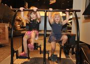 Sisters (left) Lily and Madison Page pedal at miSci's generator exhibit.