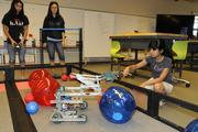 """From left, students Leah Toma, Jane Pak and Rachael Ridao play """"Toss Up"""" with VEX Robotics in the robotics bab of the of the new Sullivan Center for Innovation and Leadership at Iolani School.  The students are preparing for a VEX Robotics competition."""