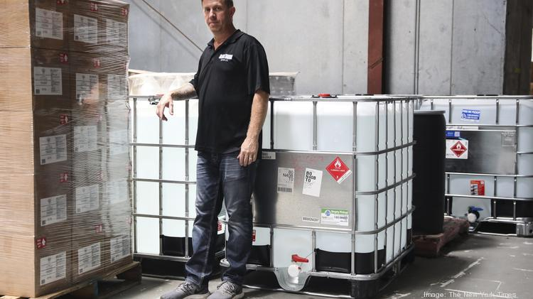 Dark Door Spirits co-owner Matt Allen, with large containers of hand sanitizer at the Dark Door Spirits warehouse in Tampa, Fla., on July 20, 2020. Dark Door Spirits creates and sells, Spirit of Clean hand sanitizer. (Eve Edelheit/The New York Times)