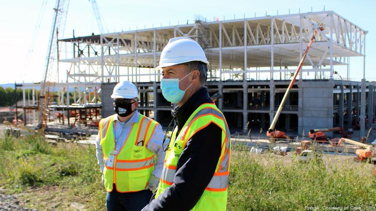 Cree CEO Gregg Lowe, center, visited Utica last week to check in with employees at the fab under construction, tour the site with Jeff Maidment, construction manager for Cree, and meet with local partners.