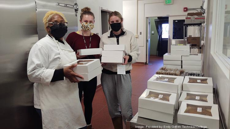 Emily Griffith Culinary Quick Start student Valerie (left) hands pies to customers before Thanksgiving.