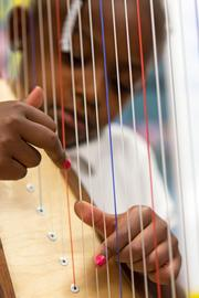 """Under the direction of instructors Jasmine Hogan and Rui Zhou, students learn to play the harp in the OrchKids program at Lockerman-Bundy Elementary School on Oct. 8. Hogan described working with the program as """"unlike teaching anywhere else"""" because of the raw energy and enthusiasm of her young students."""