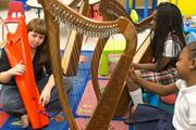 """Under the direction of Jasmine Hogan, students learn to play the harp in the OrchKids program at Lockerman-Bundy Elementary School on Oct. 8. Hogan described working with the program as """"unlike teaching anywhere else"""" because of the raw energy and enthusiasm of her young students."""