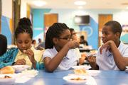 Fifth grader Ashanti Lassiter, left, and seventh graders Jada and Jonah Lassiter eat dinner at Lockerman-Bundy Elementary School on Oct. 8. In addition to providing musical and social instruction, the OrchKids program feeds the students dinner each night.