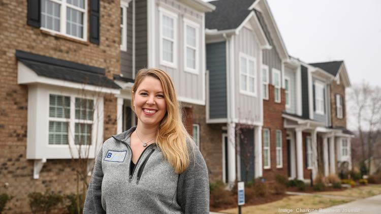 Andi Dirkschneider, vice president of land acquisition and development at Brookline Homes, is pictured with townhomes at Beatty Woods in Belmont.