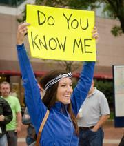 A woman cheers on runners at the start of the Baltimore Half Marathon.