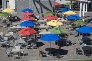 Colored umbrellas scattered across an outdoor patio offer shade from the sun and heat. Relax while you pack on the Google 15 from all the free food. Want to know what other perks Google offers?