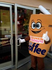 An employee dons a corporate costume for the morning rush at Dunkin' Donuts in Olathe.