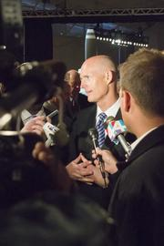 Gov. Rick Scott talks with reporters at the ribbon-cutting for Embraer's aircraft assembly hangar at Jacksonville International Airport.