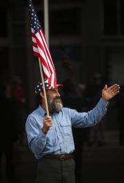 Dave Kannapell waves at the parade processional as it moves down Fourth Street, from Chestnut Street to Main Street. Kannapell, whose father served in World War II, said he was attending the parade to support both his family and veterans as a whole.