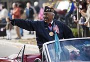 Thomas Cork, a Korean War veteran and recipient of the U.S. Marine Corps Congressional Gold Medal, points to the crowd gathered along Fourth Street on Monday.