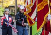 Sue Schonberger and Paul Schmitt wave flags in support of veterans at the parade.