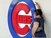 A fan poses with a Cubs logo outside Wrigley Field, home of the Chicago Cubs in 2009.