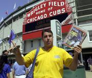 Matt Smerge hawks programs to the game between the Chicago Cubs and the St. Louis Cardinals outside Wrigley Field on Aug. 30, 2002. Major League Baseball avoided its ninth labor shutdown in 30 years with a last-minute agreement on a contract that included steroid testing and a tax on high-payroll teams aimed at slowing the growth of salaries.