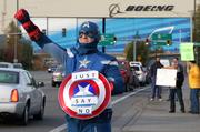 """James """"Captain America"""" White waves to cars passing by the Boeing Everett plant.  White is an inspector on the Boeing 777 line and plans to vote no on the contract offer.  """"It (the contract) is pretty insulting,"""" said White.  Hundreds of IAM local 751 machinists attended a vote no rally at the International Association of Machinists & Aerospace Workers Local 751 union hall in Everett."""