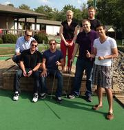 Infotrust employees play a round of mini-golf.