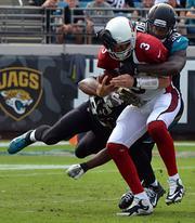 Jacksonville jaguars defensive lineman Jeremy Mincey, left, and defensive end Andre Branch sack Arizona Cardinals quarterback Carson Palmer.