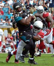 Jacksonville Jaguars running back Maurice Jones-Drew tries to escape from being tackled by Arizona Cardinals linebacker Karlos Dansby.