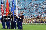 The United States military servicemen hold the American flag, the United States military branches' flags and rifles before the start of the game between the Jacksonville Jaguars and the Arizona Cardinals.