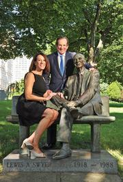 In 1988, Lewis Swyer dies at 70. Swyer was the founder of L.A. Swyer Construction Co. which built Stuyvesant Plaza, the amphitheater at Saratoga Performing Arts Center, and the Twin Towers in downtown Albany. Pictured here are siblings Carol and Edward Swyer, photographed in August with the statue of their father Lewis Swyer in Albany's Academy Park.