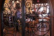 Nikolaos Sarlis, general manager works behind some of the iron decorations in the main dining area.