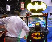 Business man checking out a Batman arcade game. That's what IAAPA's all about.
