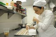 Ginger Elizabeth Hahn  pipes macaron batter onto cookie sheets at her West Sacramento kitchen.