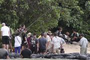 """A crew films, from left, Josh Hutcherson as Peeta Mellark, Sam Claflin as Finnick Odair, and Jennifer Lawrence as Katniss Everdeen and in a scene from """"The Hunger Games: Catching Fire"""" at Kawela Bay near Turtle Bay Resort on the North Shore of Oahu. The bay was one of several sites in Hawaii were filming took place."""