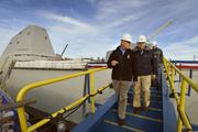 Secretary of Defense Chuck Hagel departs on the forward brow after touring the USS Zumwalt, DDG-1000, at Bath Iron Works.