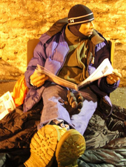 A Covenant House supporter sleeps on a cardboard box to raise awareness for homelessness.