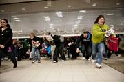 Black Friday shoppers duck under the opening door of a Sears store at Simon Property Group Inc.'s Great Lakes Mall in Mentor, Ohio. Black Friday, traditionally the biggest U.S. shopping day of the year, got off to its earliest start ever as retailers tried to woo shoppers with discounts and early store openings.