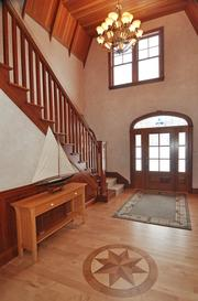 The front entrance features maple flooring and custom woodwork.
