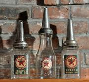 Antique motor oil dispensing bottles are displayed on the mantel.