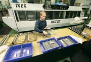 Greg Angert sorts cleaned, metal-stamped components at Penn United Technologies Inc.